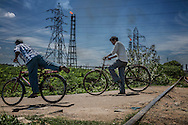 Men ride home to their community beside a petro-chemical plant beside the Buckingham Canal, constructed in 1806 to connect the backwaters along the Tamil Nadu coast.  Chennai, Tamil Nadu, India.  According to the Hindu Newspaper, the Buckingham Canal is the most polluted of Chennai's three main waterways with 60% of the 55 million litres of untreated sewage released in Chennai, not to mention industrial contamination.