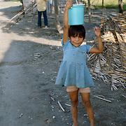 Shipibo Indian girl carrying water in village on shores of Ucayali River, Peru. Shipibo language belongs to the Panoan family.