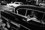 Edwin hangs out the window of his father's '53 Chevrolet Bel Air on the corner of Evergreen and Stanhope in Bushwick, NY.