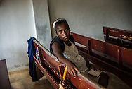 SABANETA DE YÁSICA - JUNE 27, 2015: Adrien Landia, 22, a Haitian at risk of being deported under law 169-14 takes a break between singing hymns at a church in the Cementerio neighborhood. For decades, this small riverside hamlet, divided evenly between Dominicans and Haitians, has been a peaceful and harmonious place. Proximity smothered prejudice – working side by side, sharing property and raising families together kept tensions in check.  But that is changing now, as a government plan to deport illegal Haitian migrants has started to fray the unity that once bound Cementerio, named for the small cemetery by the Yasica River where the founders of this former cattle town were buried. The policy has forced people to take a side, in anticipation of what is to come: at some point, the government will begin forceful deportations of their Haitian neighbors. PHOTO: Meridith Kohut for The New York Times