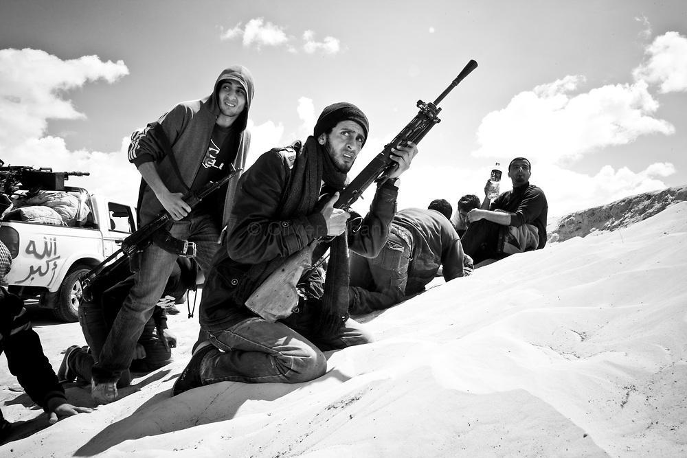 Des combattants rebelles se protègent pour éviter les tirs de l'armée loyaliste, le 22 mars 2011 à une dizaine de kilomètres d'Aj Dabiya sur la ligne de front.