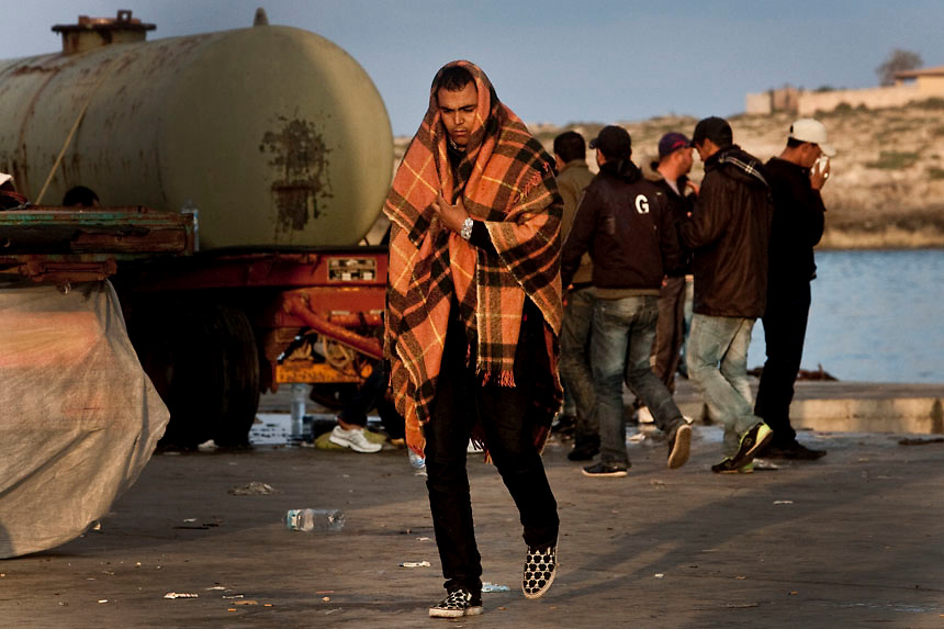 A North African refugee take shelter from the cold  on the Island of Lampedusa.The San Marco ship arrived on Wednesday and will accommodate some 1,000 immigrants who have arrived in Lampedusa from Tunisia.The Island of Lampedusa is curently overcrowded  with more than 5000 thousands immigrants from Tunisia.