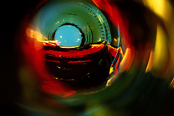 """Beauty at the Bottom: Red Wine 2""- This image is a photograph of a wine bottle shot right down the mouth of the bottle. A television provides the main light source."