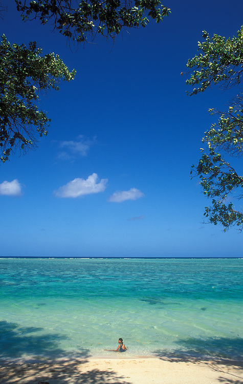 Marshall Islands, Micronesia: young girl sitting in ocean at Laura Beach on Majuro atoll.