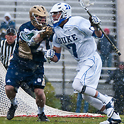 Duke midfielder Jake Tripucka #7  pushes ball from behind the goal. The third-ranked Fighting Irish defeated sixth-ranked Duke, 13-5, in men's lacrosse action on a snowy Saturday afternoon at Koskinen Stadium in Durham, N.C.