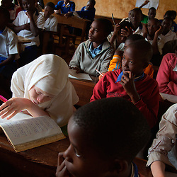 Children read and learn during class at the Kabanga Protectorate Center and School in Tanzania. Residents with albinism make up roughly one-third of the center's population—and 60 percent of them are children. Though violence against children and adults with albinism has been a problem, these kids face an even greater threat: Skin cancer kills 98 percent of Tanzanians with albinism before they reach the age of 40.