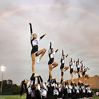 With a rainbow visible in the clouds above, Monroe-Woodbury cheerleaders perform before the start of a football game at Middletown on Friday, Sept. 3, 2010.