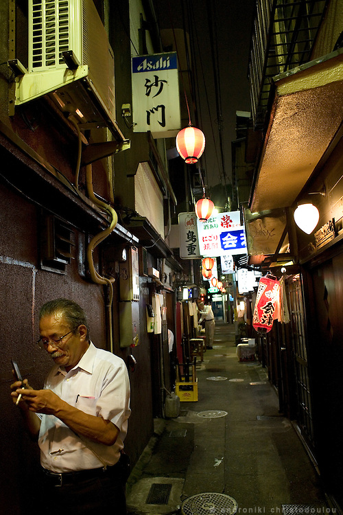 Man on the phone at Nonbei street. Nonbei street in Shibuya is a narrow street with little restaurants and bars, each one with a special character. Tokyo 16 September 2008, Japan