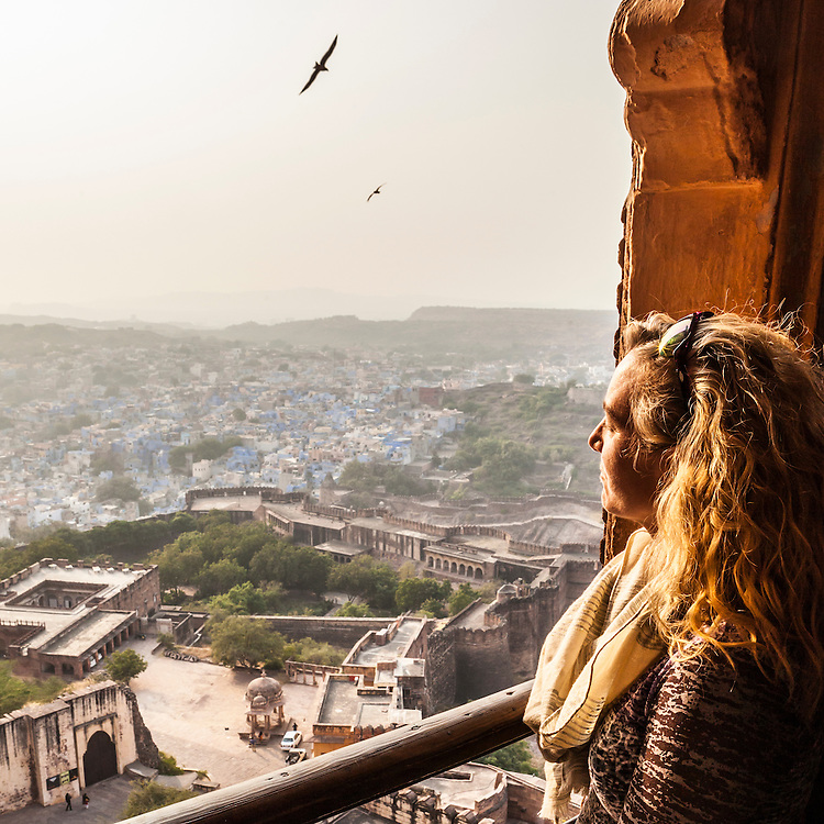 A woman looks out over the city of Jodhpur from a window high in Mehrangarh Fort. Rajasthan, India.