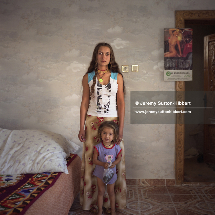 """Cassinca, a young Roma woman, stands with her daughter in one of the rooms of her new house. For the photograph Cassinca has taken off her headscarf which shows she is married, and let her hair down, to be more """"Western"""" in appearance..."""