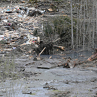A rescue worker walks through the giant mudslide near Oso, Washington as efforts continued to find victims March 26, 2014. The death toll from a weekend landslide in Washington State looked set to rise on Wednesday but officials say some of the scores of people listed as missing may have been double-counted or slow to alert family of their whereabouts. REUTERS/Rick Wilking(UNITED STATES)