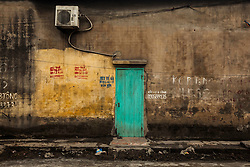 Tuquoise door opens on a grey facade, Man Xa Village, Northern outskirts of Hanoi, Vietnam, Southeast Asia