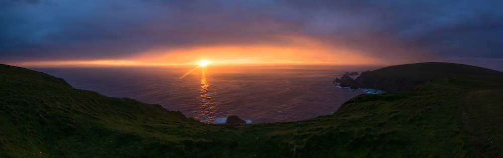 The nearly summer solstice sun setting over Hermaness National Nature Reserve on Unst, Shetlands