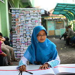 Teacher Amelia Deti, 26, sits at a circumcision registration table in Bandung, Indonesia on April 23, 2006. She was circumcised just three years earlier. The families of 248 girls were given money to have their children circumcised in this mass circumcision celebration timed to honour the Prophet Mohammed's birthday. While religion was the main reason for circumcisions, it is believed by some locals that a girl who is not circumcised would have unclean genitals after she urinates which could lead to cervical cancer. It is also believed if one prays with unclean genitals their prayer won't be heard. The practitioners used scissors to cut the hood and tip of the clitoris. The World Health Organization has deemed the ritual unnecessary and condemns such practices.