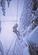 American mountainaeer Kitty Calhoun rappels from the top of a frozen waterfall in stormy winter conditions near Merkigil Iceland.