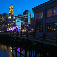 Boston North End Christopher Columbus Waterfront Park photography at night from New England Photography Guild member and award winning photographer Juergen Roth showing city landmarks such as the Boston Custom House of Boston, the waterfront and parts of the Columbus Park and Boston Marriott Long Wharf hotel as well as parts of Joe's American Bar and Grill. The Boston skyline was photographed on a beautiful spring sunset. <br />