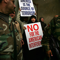 A woman holds an anti-American poster, Beirut, Lebanon, March 8, 2005. Hundreds of thousands of pro-Syrian protesters gather and chant anti-American slogans. Hezbollah, the militant Shiite Muslim group, called for a nationwide demonstration against foreign intervention and to counter weeks of massive anti-Syrian rallies.