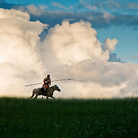 A Mongolian horsemen on his horse dressed in traditional clothing and carrying his Uurga (herding pole) silhouetted by puffy golden sunlit clouds in the grasslands of Inner Mongolia, China.
