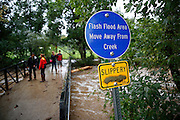 BOULDER, CO - SEPTEMBER 13: Local residents check out the raging waters of Boulder Creek as heavy rains for the better part of week fueled widespread flooding in Boulder, Colorado on September 13, 2013. Multiple signs along the creek warn of flash flooding risks. (Photo by Marc Piscotty/ © 2013)