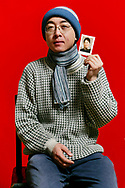 Zhang Weiwei, 29, a musician, holds an old photograph of his mother, which was colored by hand as he poses for a portrait in Beijing, China. His parents in impoverished western China don't understand why he chooses to live an artist's life instead of settling down in a stable government job.
