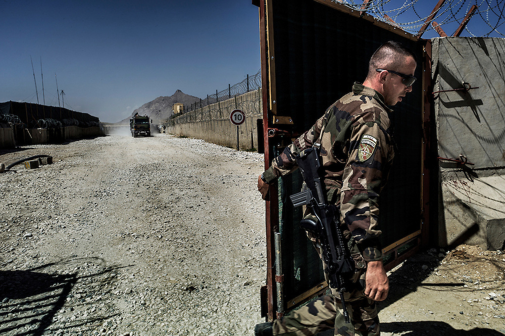 A French soldier opens the gate to the Nejrab base on September 21, 2012. The 16th BC unit from Bitche (Moselle) had left that morning to join the Nejrab base with all hardware in contenairs. They will depart in the afternoon for the Warehouse French base in Kabul, where they will spend a week disassembling their weapons, cleanning their tanks and preparing their departure for France. AFP PHOTO / JEFF PACHOUD