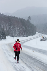 A woman running on NH 16 in New Hampshire's White Mountains on a snowy winter day.