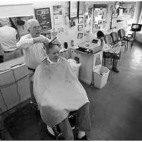 Lee Wyman has his hair cut by James Paige at Paige's Barbershop on Dickinson Avenue.