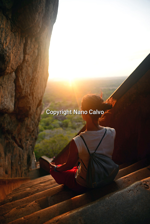 Young woman sits in lotus pose in the stairs up to the Ancient City of Sigiriya, Sri Lanka