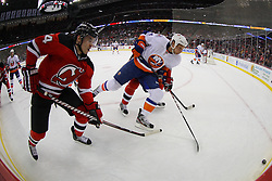 Apr 3; Newark, NJ, USA; New Jersey Devils center Adam Henrique (14) and New York Islanders defenseman Mark Eaton (4) battle for the loose puck during the first period at the Prudential Center.
