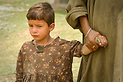 Boy holding his mother's hand in Kashmir, India