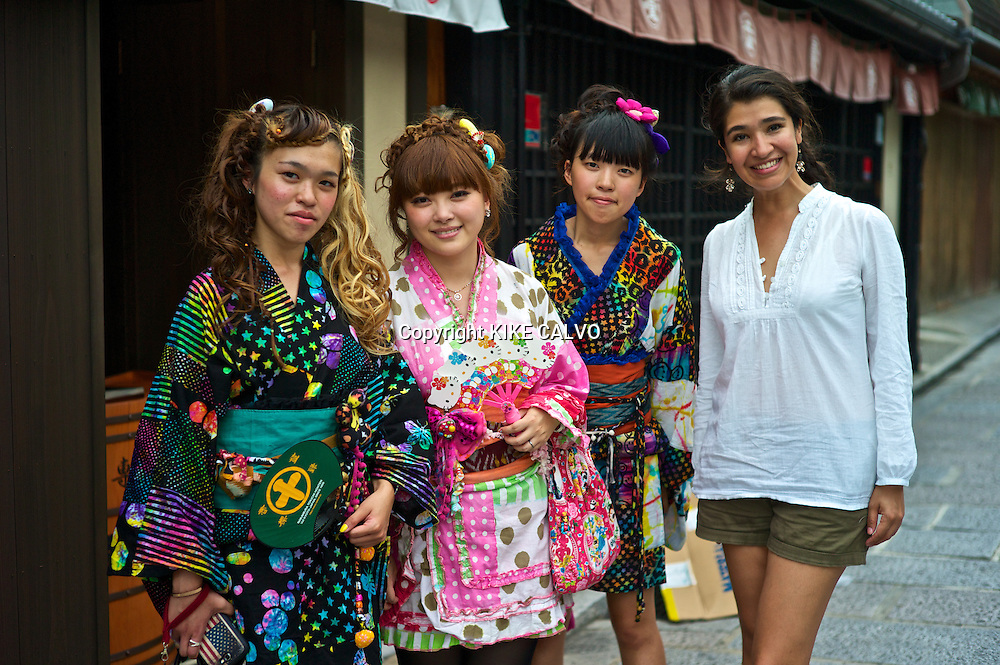 Asian teens wearing a modern colorful version of the traditional kimonos pose for a memory photo with a tourist, while exploring the stores and shops near the Kiyomizu Temple.