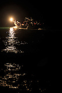 A fire fishing boat looks for fish off Taiwan's north coast.