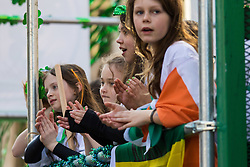 London, March 13th 2016. The annual St Patrick's Day Parade takes place in the Capital with various groups from the Irish community as well as contingents from other ethnicities taking part in a procession from Green Park to Trafalgar Square.  PICTURED: Children applaud from the back of a float. &copy;Paul Davey<br /> FOR LICENCING CONTACT: Paul Davey +44 (0) 7966 016 296 paul@pauldaveycreative.co.uk