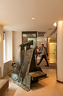"""Lynn Chadwick's sculpture """"Sitting couple on bench"""" in Christie's King street lobby with Colin the doorman."""