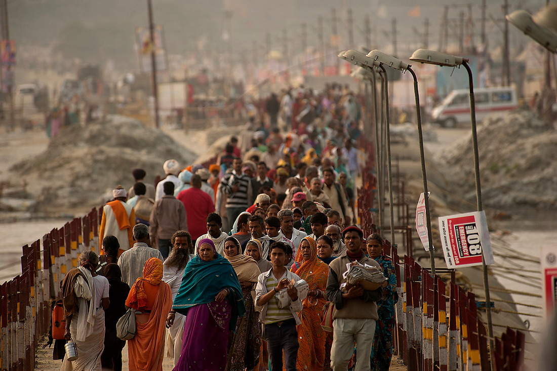 Hindu pilgrims cross one of the and 10 pontoon bridges that are laid across the Ganges on February 6, 2013 in Allahabad, India during the Kumbh Mela. — © Jeremy Lock/