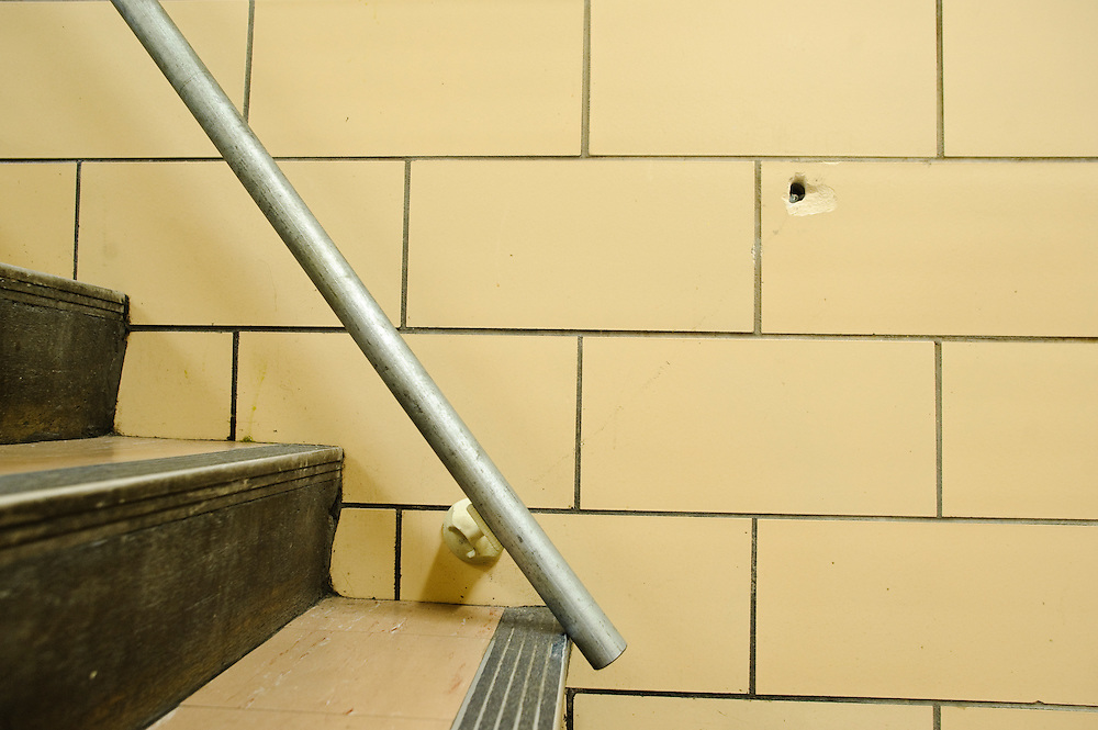 (photo by Matt Roth).Friday, May 14, 2010..One of the stairwell rails has become unbolted from the wall. There are several more holes lining the school's stairs, marking where rails used to be. ..The building housing the Baltimore Freedom Academy, a grade 6-12 Baltimore public charter school focusing in social justice, was built in 1960. Fifty years later, the school is in disrepair. Old pipes make water from the fountains undrinkable. Asbestos makes repairing/replacing the pipes a hazard. The school has no air conditioning which makes the year-round school unbearable in the summer. The most derelict area is the boys locker room, where students are not allowed.