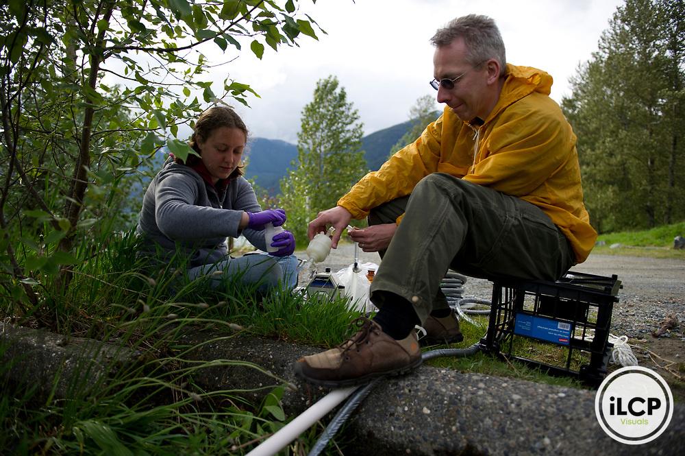 Graduate student Britta Voss and Dr. Bernhard Peuker-Ehrenbrink sample the waters of Harrison Lake.