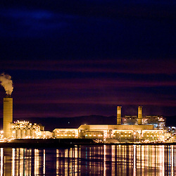 The Four Corners Power Plant is reflected in Lake Morgan in Fruitland, N.M.