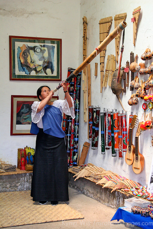 Americas, South America, Ecuador, Peguche. Ecuadorian woman demonstrates musical instrument of the Andes.