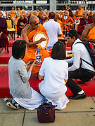 "22 FEBRUARY 2016 - KHLONG LUANG, PATHUM THANI, THAILAND:  A monk talks to devotees during the Makha Bucha Day service at Wat Phra Dhammakaya.  Makha Bucha Day is a public holiday in Cambodia, Laos, Myanmar and Thailand. Many people go to the temple to perform merit-making activities on Makha Bucha Day, which marks four important events in Buddhism: 1,250 disciples came to see the Buddha without being summoned, all of them were Arhantas, Enlightened Ones, and all were ordained by the Buddha himself. The Buddha gave those Arhantas the principles of Buddhism, called ""The ovadhapatimokha"". Those principles are:  1) To cease from all evil, 2) To do what is good, 3) To cleanse one's mind. The Buddha delivered an important sermon on that day which laid down the principles of the Buddhist teachings. In Thailand, this teaching has been dubbed the ""Heart of Buddhism."" Wat Phra Dhammakaya is the center of the Dhammakaya Movement, a Buddhist sect founded in the 1970s and led by Phra Dhammachayo.     PHOTO BY JACK KURTZ"