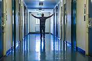 A prisoner walking with his arms out  down one of the corridors of the enhanced wing at <br /> HMP/YOI Portland, Dorset. &copy; Prisonimage.org All image use must be agreed first. All images must be creditied.
