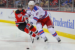 Sep 16, 2013; Newark, NJ, USA; New York Rangers defenseman John Moore (17) skates with the puck while being defended by New Jersey Devils right wing Mike Sislo (56) during the second period at Prudential Center.