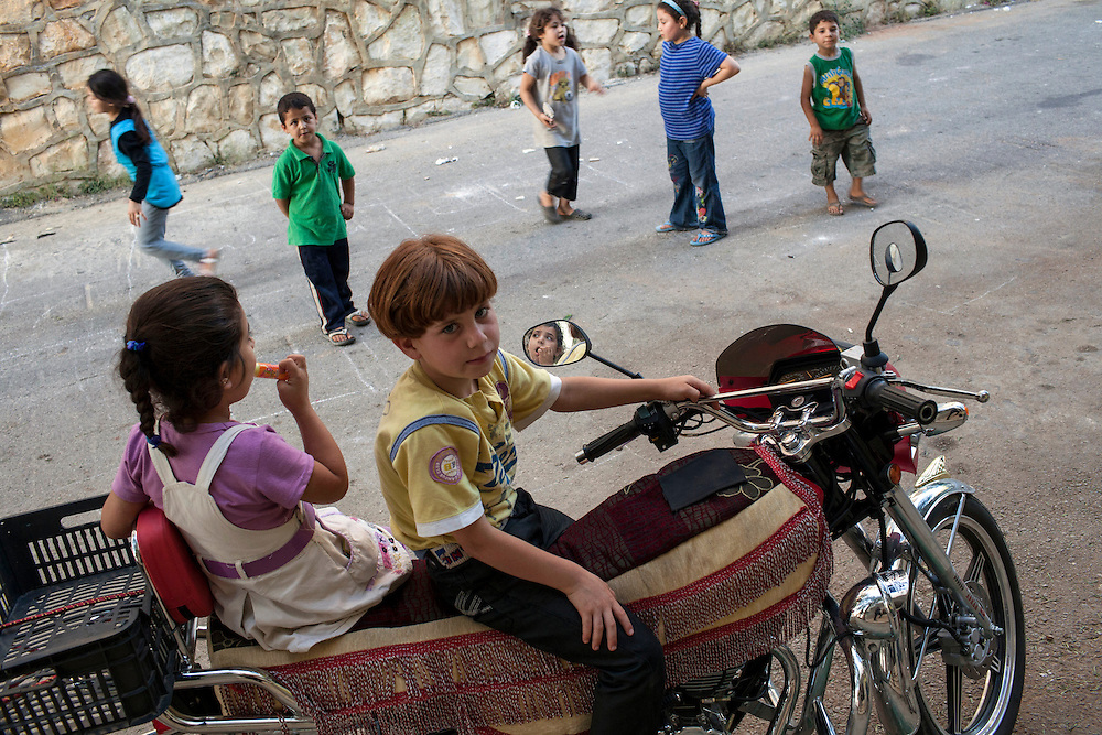 05/07/2013 near Damour, Lebanon:A young Syrian boy plays on a motorcycle with friends. Estimates have placed the number of Syrian refugees in Lebanon at well over 500,000 people.