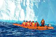 Tourits explore the icy water at Portal Point in Antarctica, passing in front of a blue iceberg. Model Released photo.