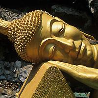 Asia, Laos, Luang Prabang, Statue of Reclining Buddha at shrine near Wat Tham Phu Si Buddhist temple