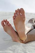 bare feet on a white sand dune