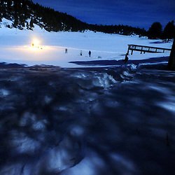 Revelers head down to the bar on McGaffey Lake during a winter full moon party in the mountains of western New Mexico.