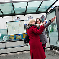 A woman gives another woman directions at a bus stop in Vilnius, Lithuania