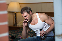 man smoking in a cheap motel bed