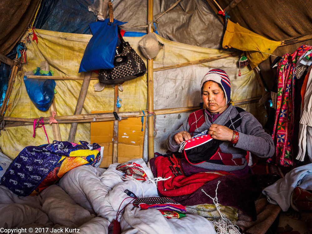 04 MARCH 2017 - KATHMANDU, NEPAL: A woman works in her unheated tent in an IDP camp in the center of Kathmandu. She was making hats and clothes to sell to tourists around Durbur Square in Kathmandu. The camp opened days after the April 2015 earthquake devastated Nepal, killing almost 9,000 people. At its peak, about 1,800 families lived in the camp. The camp is still open nearly two years after the earthquake, about 400 families currently live in the camp. Camp residents say the Kathmandu municipal government is trying to close the camp and is encouraging residents to find new housing. They said the government is cutting off services to the camp and last week stopped the free distribution of water, although water can be purchased for delivery. Most of the people in the camp came to Kathmandu from rural villages in the mountains in the weeks after the earthquake. Many of the residents of the camp, technically homeless, have found work in Kathmandu's bustling construction industry, rebuilding homes destroyed in the earthquake.       PHOTO BY JACK KURTZ
